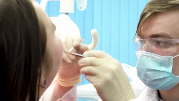 Close up for teeth checkup at dentist office with special equipment. Man dentist examining teeth of a young woman sitting in a chair, dental care concept.
