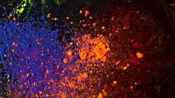 Jasně barevný výbuch prachu na černém pozadí, koncept umění. Pohyb modrých a oranžových inkoustových barev, vícebarevné a světlé textury.
