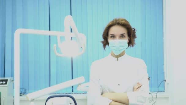 Zubař žena nosí masku v zubní ordinaci. Média. Atraktivní žena zubař v maska a plášť je připraven k práci. Zubní koncepce