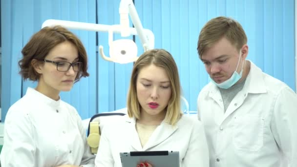 Team of doctors discuss diagnoses of patients. Media. Doctors together analyze tests and diagnoses of patients on background of hospital room with lamp