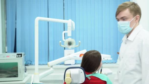 Zubní lékař konzultuje s pacientem. Média. Mužské asistent stojí v uniformě a masku na pozadí zubař diskuse o zacházení s pacientem