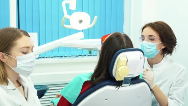 Close-up of medical dentist team in dental office treating teeth of female young patient. Dental care.