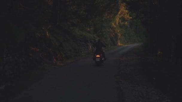 Zadní pohled na muže na motocyklu. V UK. Muž na motocyklu na lesní asfaltovou silnici