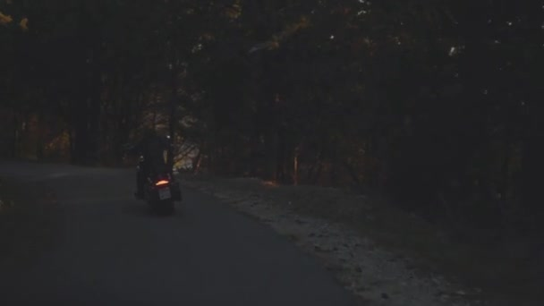Nézet hátulról egy ember lovaglás egy motorkerékpár. Stock. Ember lovaglás egy motorkerékpár, erdei Aszfalt úton