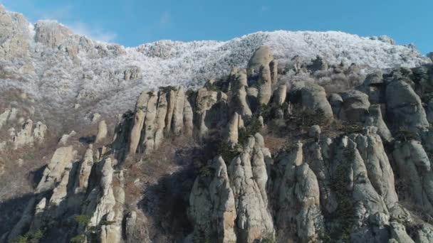 Obrovské a bizarní tvary horských skal obklopená zasněžované keřů a stromů proti modré obloze. Střela. Detail.