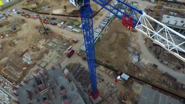 Top view of construction site with crane. Scene. Crane stands above roofs of buildings on construction site with standing cars on street. Urban construction of residential buildings