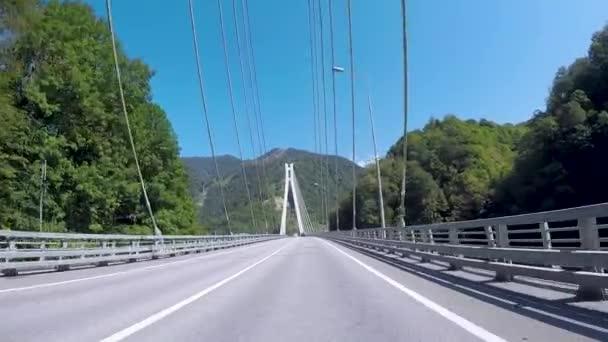 Most s dráty. Scénu. Krásný výhled na zelené kopce a modrá obloha, procházející moderní bílé visutý most. Letní cestování autem
