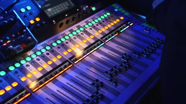 Close-up di uomo in piedi vicino a un sound mixer console con un sacco di pulsanti. Filmato di repertorio. Musics suono impostazione