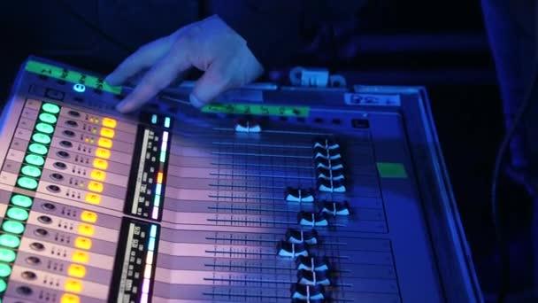 Close-up della mano Mans impostazione di un sound mixer console. Filmato di repertorio. Sta regolando i livelli sonori e spingendo diversi pulsanti