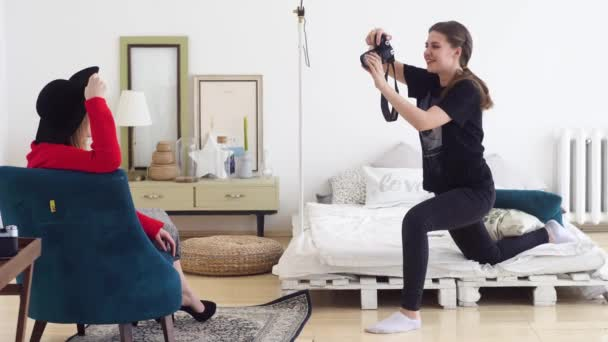 Fotografo femminile e modella scattare foto romantiche in studio fotografico. medio. Fotografia in interni delicati con modello seduto in cappello e camicetta luminosa in poltrona
