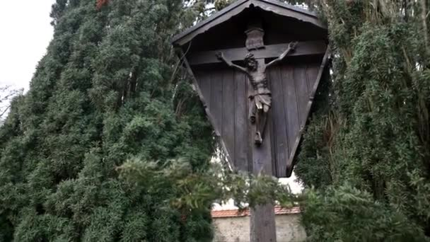 Wooden landmark with Christ crucified on cross. Art. View of wooden monument of crucified Jesus Christ standing between green dense trees and bushes