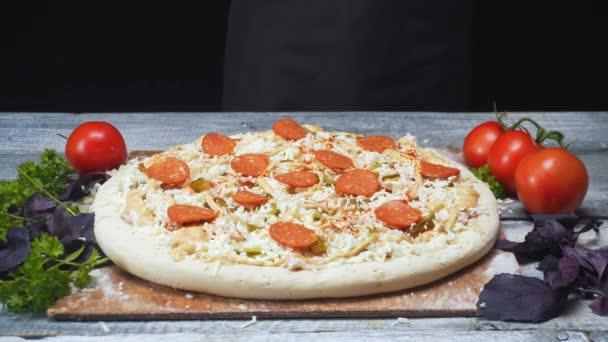 Na dřevěném tabuli u rajčat, petržel a bazalky najdete kousek pizzy pokrytého pizzou a sýrem. Rámeček. Vynikající příprava pizzy