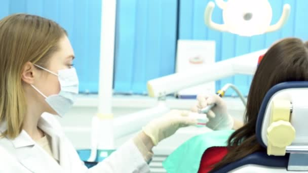 Professional dental cleaning of female patient teeth at dental clinic, medicine concept. Media. Women dentists doing the procedure of teeth cleaning and polishing at the dentist office.