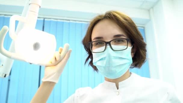 Patientensicht eines Zahnarztes, der den Mund des Patienten untersucht, modernes zahnmedizinisches Konzept. Medien. junge Zahnärztin blickt auf die Patientin und dreht die Lampe.