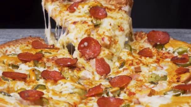 Közelről a kézi vesz egy szelet pizza a stretching mozzarella fekete háttér, foodporn koncepció. Keret. Kézzel vesz egy szelet pepperoni sajtos pizza feküdt az asztalra.