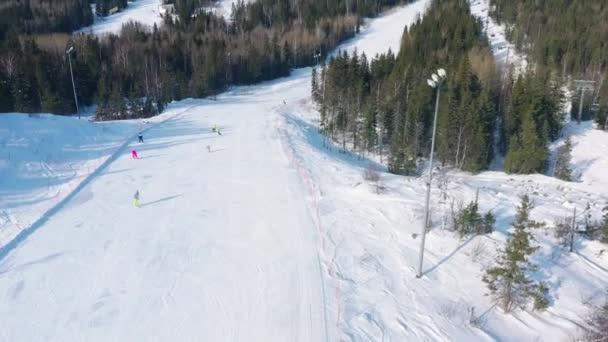 Letecký pohled na lidi na lyžařské dráze s jehličnaté stromy z obou stran trati. Záběry. Lyžařské středisko