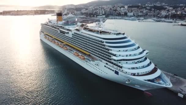 Krásná bílá výletní loď v zálivu, letecký výhled. Akcií. Malebný pohled na přístav, Mořský břeh a velkou výletní loď s lidmi na palubě.