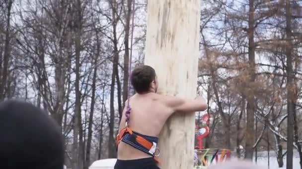 Man climbs the pole on the carnival. Clip. Person climbs on pole behind gifts while Shrovetide festivities