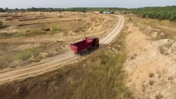Aerial for the red big truck driving in ground quarry with flying dust behind it, industry concept. Scene. Empty lorry moving on country road with green forest on the background.