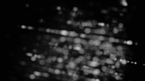 Rozmazané monochromatické pozadí s rotujícími paprsky malých kruhů, bezešvé smyčky. Animace. Rotující bílé a šedé řádky teček na černém pozadí.