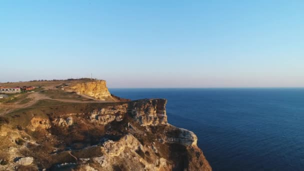 Aerial view of people standing on a large cliff against blue clear sky and blue sea water. Shot. Beautiful view from above