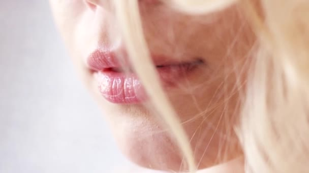 Close-up view of beautiful young woman face with perfect skin, pink lips and blonde hair on the white background. Action. Women images concept