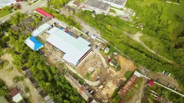 Az ipari területek felülnézete gyári épületekkel. Akció. Falusi ipari területek, nyáron zöld fával