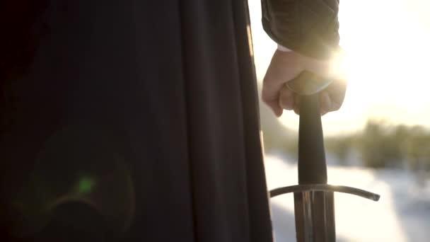 Mann im mittelalterlichen Anzug mit Schwert. Aktion. Nahaufnahme einer Hand im mittelalterlichen Anzug, die ein Schwert vor dem Hintergrund des Sonnenlichts hält. Epischer Blick auf mittelalterlichen Helden