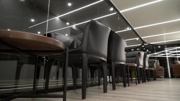 Pracovní židle a stoly pro dva v luxusní restauraci. Akce. Pohled na luxusní moderní restauraci s obchodními stoly a koženými židlemi v bílém a černém lesklém interiéru