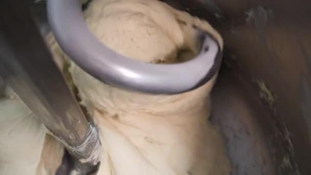 Közelről a tészta dagasztás a kenyér pékáru gyár. Stock Footage. Kenyér keverő pékségben, péksütemények és bagettet.