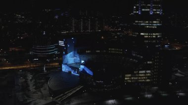 Beautiful aerial view of illuminated modern buildings, business centers and road in the city center at night. Action. City nightlife