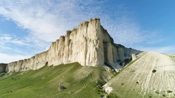 Pohled na vysoký bílý kámen na modrém oblačském pozadí. Shot. Slunečný den a krásná zelená louka na úpatí hory, krása přírody.