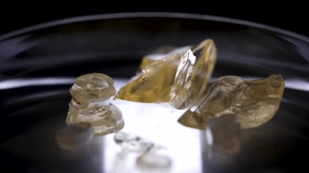 Nádherné zlaté kameny ležící v Petriho misce na černém pozadí. Skladní záběry. Uzavřít pro béžové krystaly ležící na skleněném stojanu, geologická koncepce.