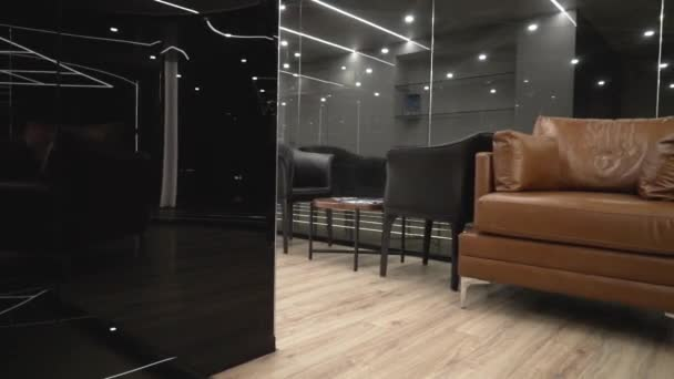 Moderní drahý interiér s pohovkou a černým sklem. Akce. Úzký prostor s křesly a koženou pohovkou na pozadí černých serkových stěn a jasného umělého osvětlení
