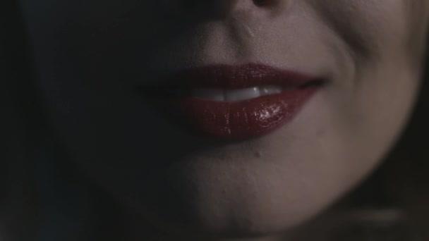 Extrémní detail, jak se sexy dívčí ústa usmívá ve tmě a tváří. Akce. Krásná mladá ženská modelka s červenými smyslými rty a bílými zuby.