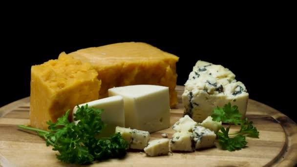 Uzavřete francouzské lahodné staré sýry, které se podávají na dřevěné desce izolované na černém pozadí. Rámeček. Čedar, parmezán a modré kousky sýra s petrželovou.