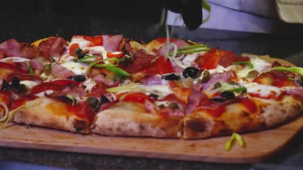 Close-up of chef preparing Italian pizza. Frame. Professional chef decorates greens with traditional Italian pizza. Tasty Italian pizza, which will have your mouth watering