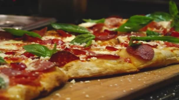 Close-up of cooked pepperoni pizza with basil leaves. Frame. Juicy fragrant pizza cooked in Italian restaurant or pizzeria. Pizza that makes your mouth water. Italian cuisine