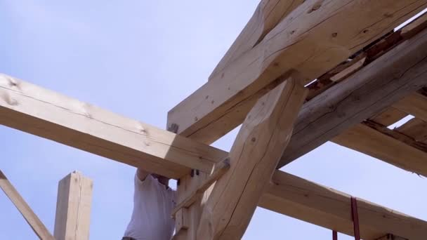 Arbeiter bauen und stapeln Bretter Holzhaus. Clip. Arbeiter montieren schöne Holzbalken auf der Baustelle des Hauses. Holzhaus im Baumodus auf dem Hintergrund des Himmels