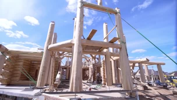 Krásný výhled na budovu pod výstavbou dřevěného domu. Klip. První stavba dřevěného domu na modrém nebeském pozadí. Rám dřevěných kulatiny