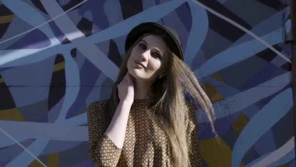 Portrait of young beautiful fashionable woman with black hat posing on blue graffity background. Action. Model wearing stylish wide-brimmed hat looking at camera, female fashion.