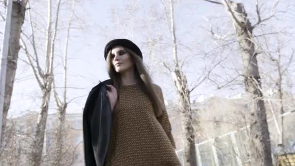 Buttom kilátás a stílusos csinos nő gyalogos kültéri fekete bőrdzseki és egy kalap ősszel. Akció. Modell lány visel barna blouze, utcai divat.