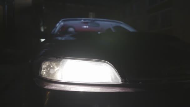 Když se v noci vypíná světlo zaparkované auta, zavřete je. Akce. Podrobnosti o vozidle, předním nárazníku a čelním světlu vozidla stojícího v blízkosti domu.