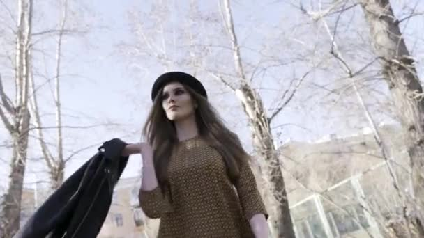 Young model girl wearing brown dress and black hat and walking in a city park with bare trees on blue sky background, bottom view. Action. Beautiful woman walking outside.