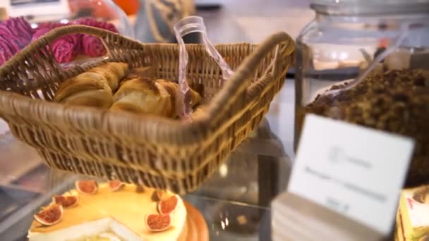 Wicker basket with French pastry standing on glass display in the bakery near fig cheesecake, food concept. Art. Homemade pastry, close up for freshly baked French croissants.