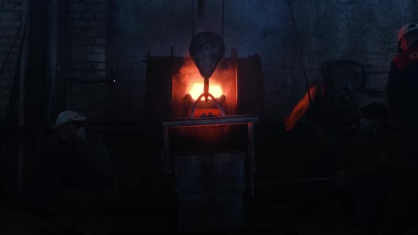 Workers poured molten metal at plant. Stock footage. Workers in form and helmets control process of pouring molten metal from boiler at metallurgical plant