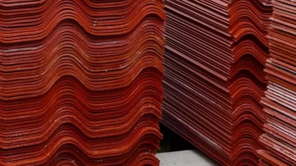 Červené střešní dlaždice, suroviny pro průmyslovou výstavbu. Skladní záběry. Sklad s červenými dlaždicemi