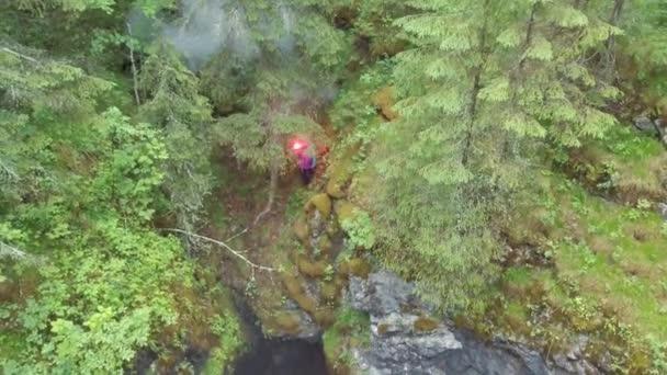 Mann, der in der Nähe der tiefen Schlucht steht, mit rotem Signalfeuer in der Hand im Wald in der Nähe der hohen alten Bäume und Sträucher. Archivmaterial. Signale im Wald