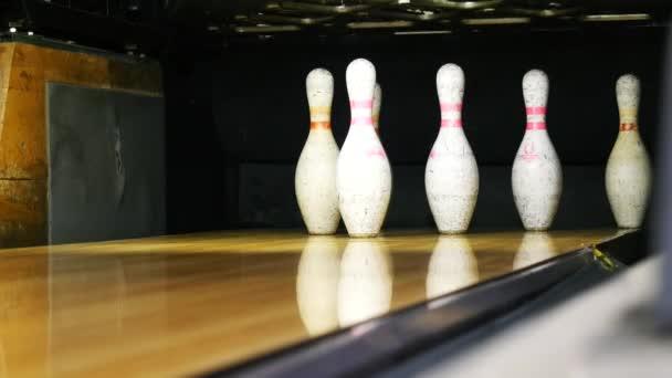 Pohled na bowlingové špendlíky, stojící na konci bowlingové uličky a kuželový míč na dřevěné ploše ve sportovním klubu. Zábavné sportovní víkendy v kuželkách