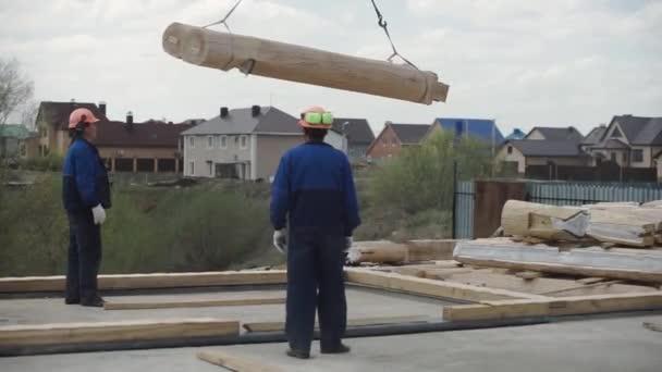 Stavitelé v uniformní a helmici pracující s popruhy ve stavebním prostoru. Klip. Dělníci pracující s jeřábem na stavbě domu